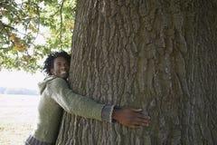Tronco de árbol feliz del abarcamiento del hombre en el parque Fotografía de archivo libre de regalías