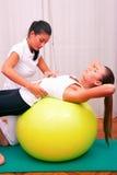 Tronco del bacino di controllo di esercizi con lo stabiliza del fitball della palla del bobath Immagine Stock