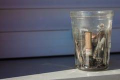 Tronconi della sigaretta in un vetro sporco Fotografie Stock Libere da Diritti