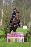 Troncos y saltos de árbol de salto de la competencia adolescente del campo a través del caballo sobre barriles de agua y de barra Imagenes de archivo