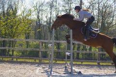 Troncos y saltos de árbol de salto de la competencia adolescente del campo a través del caballo sobre barriles de agua y de barra Imagen de archivo libre de regalías