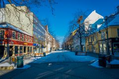 TRONDHEIM NORGE - APRIL 04, 2018: Den utomhus- sikten av de tomma gatorna med traditionella skandinaviska byggnader står Royaltyfria Bilder