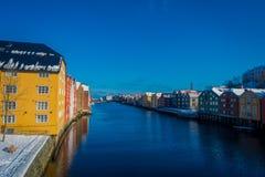 TRONDHEIM NORGE - APRIL 04, 2018: Ursnygg sikt av berömda träkulöra hus från bron i den Trondheim staden, Norge Arkivfoto