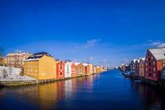 TRONDHEIM NORGE - APRIL 04, 2018: Ursnygg sikt av berömda träkulöra hus från bron i den Trondheim staden, Norge Arkivbild