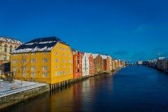 TRONDHEIM NORGE - APRIL 04, 2018: Ursnygg sikt av berömda träkulöra hus från bron i den Trondheim staden, Norge Royaltyfri Bild