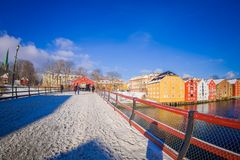 TRONDHEIM, NORWAY - APRIL 04, 2018: Beautiful outdoor view of old wooden bridge Gamle Bybro with some timber colorful. Buildings in the shore of nidelva river Stock Photography