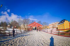 TRONDHEIM, NORWAY - APRIL 04, 2018: Beautiful outdoor view of old wooden bridge Gamle Bybro with some timber colorful. Buildings in the shore of nidelva river Royalty Free Stock Photos