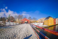 TRONDHEIM, NORWAY - APRIL 04, 2018: Beautiful outdoor view of old wooden bridge Gamle Bybro with some timber colorful. Buildings in the shore of nidelva river Stock Photo