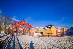 TRONDHEIM, NORWAY - APRIL 04, 2018: Outdoor view of people walking in an old wooden bridge Gamle Bybro with some timber. Colorful buildings in the shore of Royalty Free Stock Images