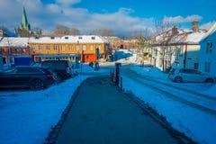 TRONDHEIM NORWEGIA, KWIECIEŃ, - 04, 2018: Niezidentyfikowani ludzie chodzi w tradycyjnym Skandynawskim drewnianym utrzymanie domó Zdjęcie Stock
