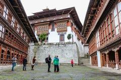 Trongsa, Бутан - 13-ое сентября 2016: Туристская группа в дворе Trongsa Dzong, Бутана Стоковое Изображение RF