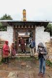 Trongsa, Bhutan - 13. September 2016: Touristische Gruppe, die mit Einheimischen bei Trongsa Dzong an einem regnerischen Tag, Bhu lizenzfreie stockfotografie