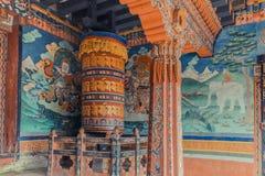 Trongsa Bhutan - September 13, 2016: Väggmålningar och stort bönhjul inom portiken av Trongsaen Dzong, Bhutan Arkivbild