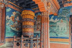 Trongsa, Bhutan - September 13, 2016: Wall paintings and large prayer wheel inside the portico of the Trongsa Dzong, Bhutan. Trongsa, Bhutan - September 13 stock photography