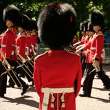 Trooping the Colour ceremony, London UK. Soldiers marching in background as one soldier in foregound stands to attention. Trooping the Colour ceremony, London Royalty Free Stock Photos