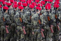 Troops with assault rifle. And red hats from their backs. Unrecognizable people royalty free stock photo
