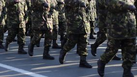 Troops Marching. Soldiers in camouflage uniform and wearing boots are marching in cadence stock video