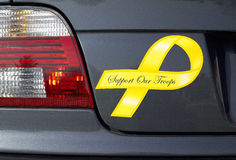Troops Yellow Ribbon. A yellow ribbon, Support Our Troops, magnet is displayed on a grey metallic car. (14MP camera stock images