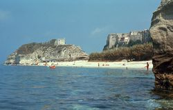 1974. Italy. Tropea, beach, Calabria. The picture shows the main beach at Tropea. In the background the holy church of Santa Maria dell`Isola Stock Photos