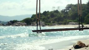 Tropeninsel-Strand und Baum-Schwingen Das Spritzen bewegt in das Meer an den Steinen auf schönem Hintergrund auf dem blauen Himme stock video