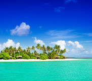 Tropeninselstrand mit Palmen und bewölktem blauem Himmel Stockfotos