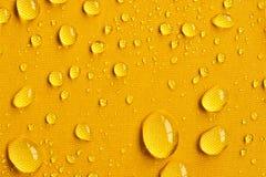 Tropfen auf gelbem Regenschirm Stockfotos
