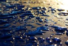 Tropfen der Wasser abweisenden Oberfläche Schwarzen u. Blau und Sonne stockbild