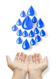 Tropfen des blauen Wassers des Konzeptes gemacht vom Papier zwei Hände auf weißem Hintergrund Stockfotografie