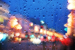 Tropfen des Regens auf blauem Glas mit städtischen defocused Lichtern lizenzfreie stockbilder