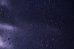 Tropfen des Regens auf blauem Glashintergrund Lizenzfreie Stockbilder