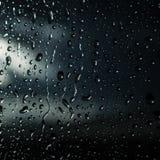 Tropfen des Regens auf blauem Glashintergrund Stockfotografie