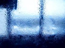 Tropfen des Regens auf blauem Glashintergrund Stockbilder
