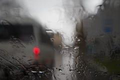 Tropfen des Regens auf blauem Glashintergrund Straße Bokeh-Lichter unscharf Autumn Abstract Backdrop Stockbild