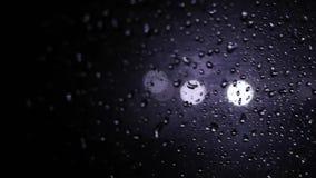Tropfen des Regens auf dem Fenster, die Nacht außerhalb des Fensters, flackerndes Licht stock video footage