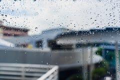 Tropfen des Regens auf einem Fensterglas Stockfotos