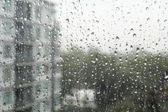 Tropfen des Regens auf einer Fensterscheibe Stockfotos