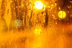 Tropfen des Regens auf Glashintergrund am gelben Licht Straße Bokeh stockbilder