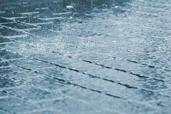 Tropfen des starken Regens auf Bürgersteigsoberfläche Stockbild