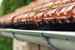 Tropfen des Wasserstroms in die Dachgesimse Stockfoto