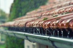 Tropfen des Wasserstroms in die Dachgesimse Stockbild