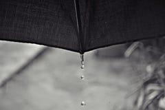 Tropfen, die vom schwarzen Regenschirm fallen Lizenzfreie Stockfotos