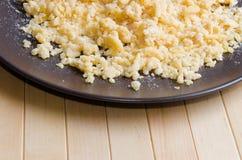 Tropfen Sie von den Eiern und vom Mehl auf der braunen Platte, die auf Hintergrund vom Holz liegt Stockfoto