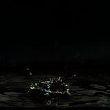 Tropfende Flüssigkeit, gebildet einem dunklen Krater und vielen Wassertropfen Lizenzfreies Stockfoto