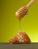 Tropfender organischer Honig mit Bienenwabe auf gelbem Hintergrund Lizenzfreie Stockfotos