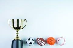 Trophée, jouet du football, jouet de base-ball, jouet de basket-ball et RU d'or Photo stock