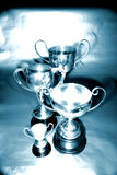 Trophies. In varying sizes with handles at side, blue and silver tones royalty free stock images