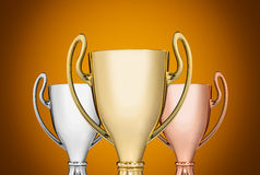 Trophies. Close up golden,silver and bronze trophies on yellow background Royalty Free Stock Images