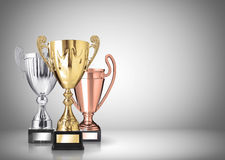 Trophies. Golden, silver and bronze trophies on gray background Royalty Free Stock Photography