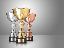 Trophies. Golden, silver and bronze trophies on gray background vector illustration