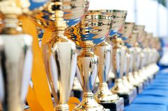 Trophies. Many shiny gold trophies in a rows Royalty Free Stock Photography